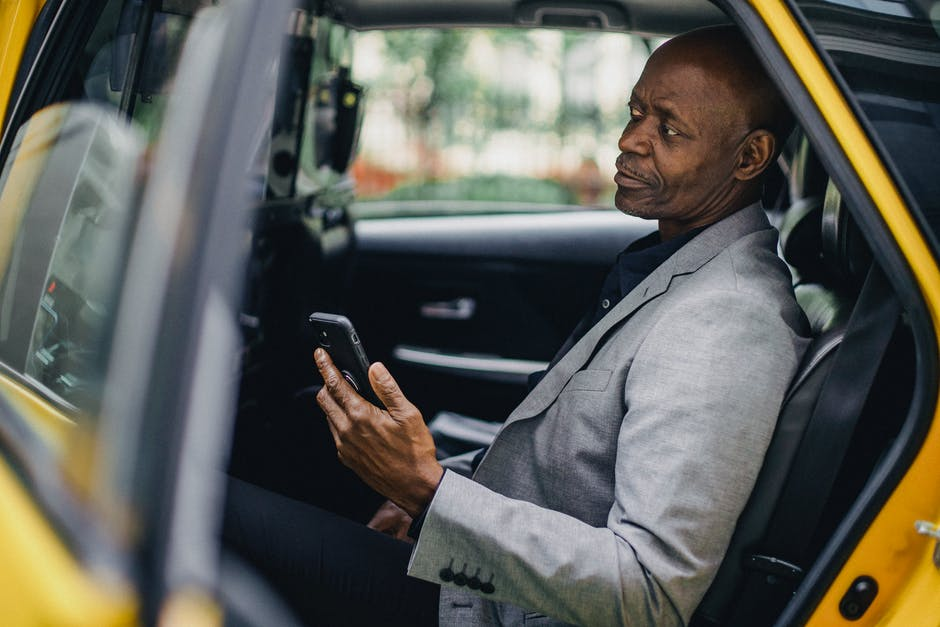 A man in a car talking on a cell phone