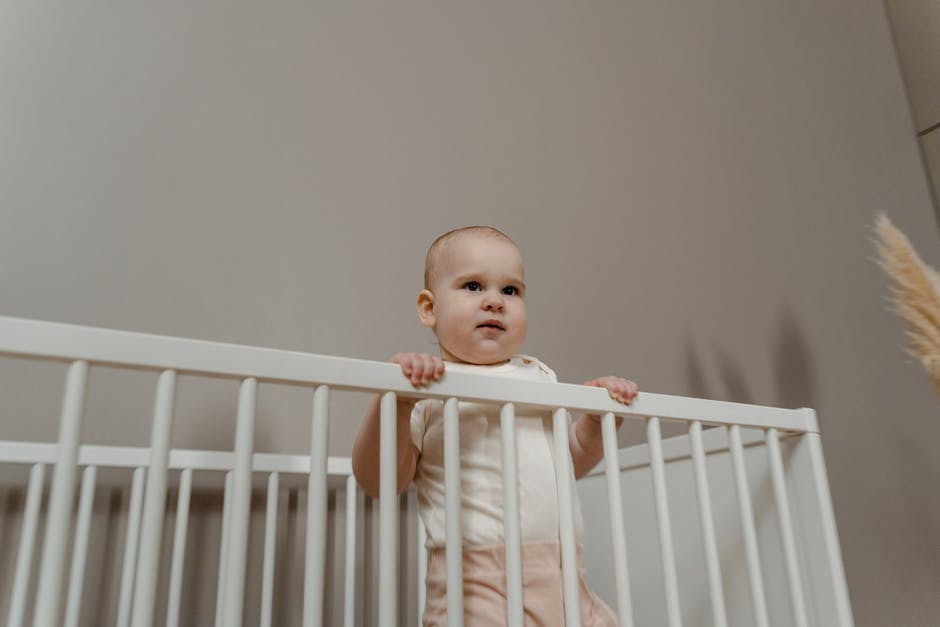 A baby girl standing in front of a fence