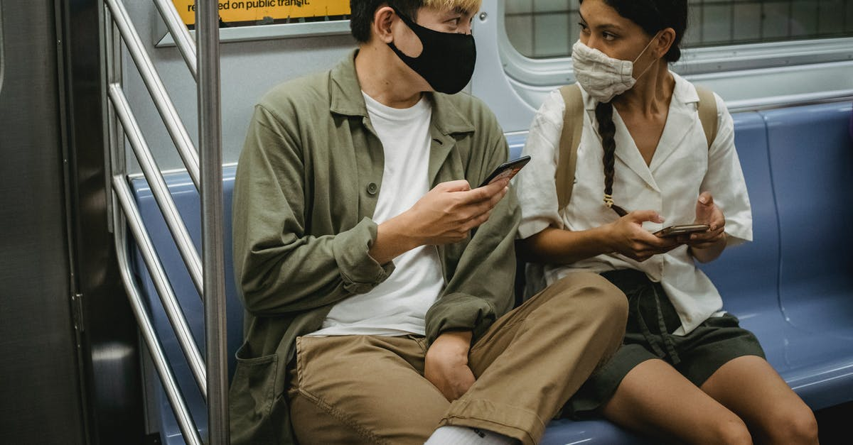 A man and a woman sitting on a subway car